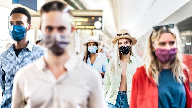 Grupo multirracial caminando con expresión seria en la estación de tren