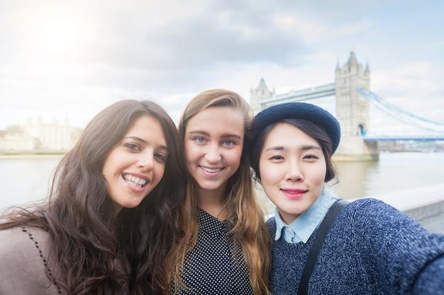 Grupo multirracial de chicas tomando un selfie en londres.