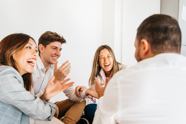 Grupo multirracial de compañeros de trabajo riendo juntos.