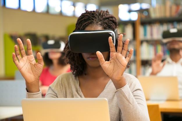 Grupo multirracial de estudiantes que usan dispositivos de realidad virtual durante la clase