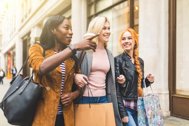 Grupo multirracial de mujeres comprando y paseando por la ciudad.