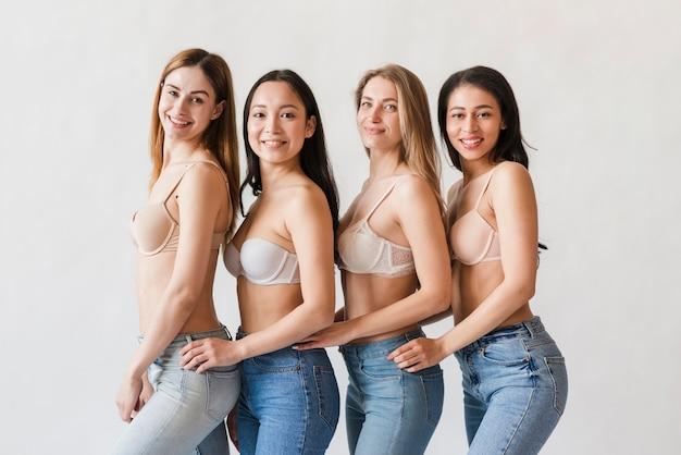 Grupo multirracial de mujeres felices posando en sujetadores