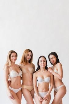 Grupo multirracial de mujeres positivas posando en lencería.