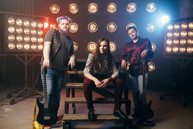 Grupo musical posa en el escenario con luces en club nocturno
