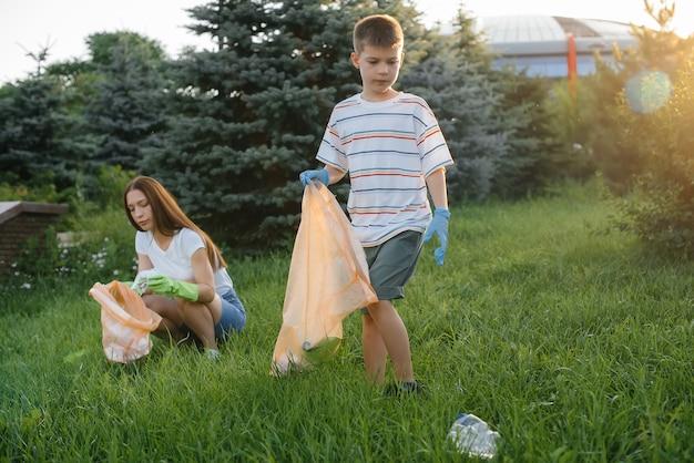 Un grupo de niñas con niños al atardecer se dedican a la recolección de basura en el parque. cuidado del medio ambiente, reciclaje.