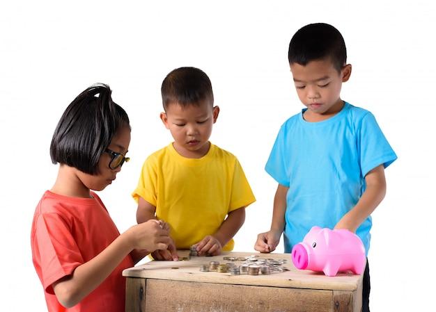 El grupo de niños asiáticos está ayudando a poner monedas en la hucha aislada en el fondo blanco