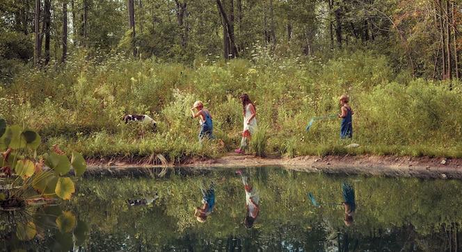 Grupo de niños caminando por un campo cubierto de vegetación y reflexionando sobre el lago bajo la luz del sol