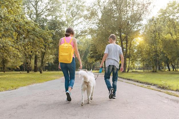 Grupo de niños caminando con perro husky blanco