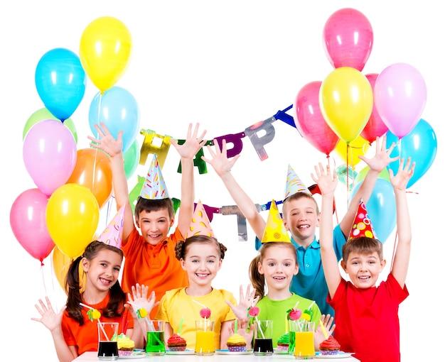 Grupo de niños con camisetas de colores en la fiesta de cumpleaños con las manos levantadas, aisladas en blanco.