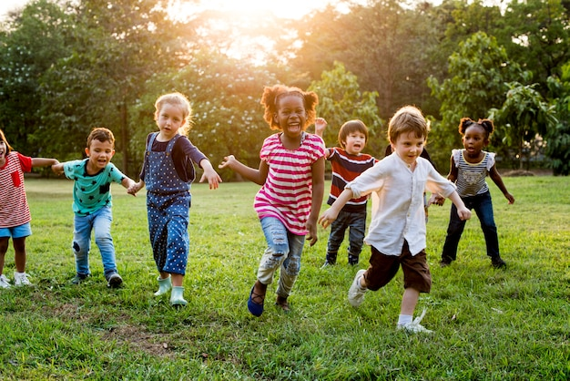 Grupo de niños diversos jugando juntos en el campo