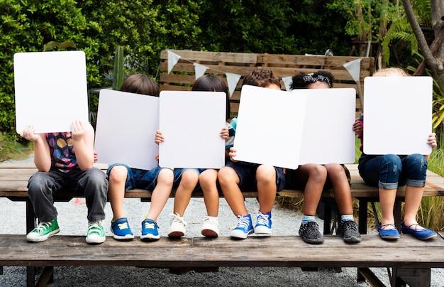 Grupo de niños diversos con pancartas.