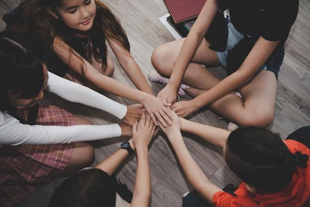 Grupo de niños diversos se unen para el trabajo en equipo, concepto de educación