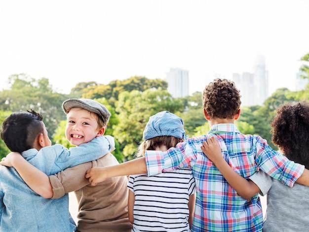 Grupo de niños diversos de vuelta los brazos juntos