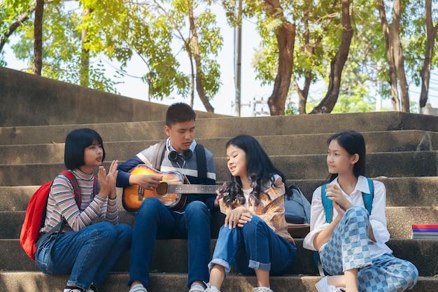 Grupo de niños estudiantes tocando la guitarra y cantando canciones juntos en el parque de verano