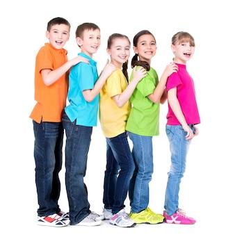 Grupo de niños felices en camisetas de colores se colocan uno detrás del otro poniendo las manos sobre los hombros sobre fondo blanco.