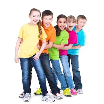 Grupo de niños felices en camisetas de colores están uno detrás del otro sobre fondo blanco.