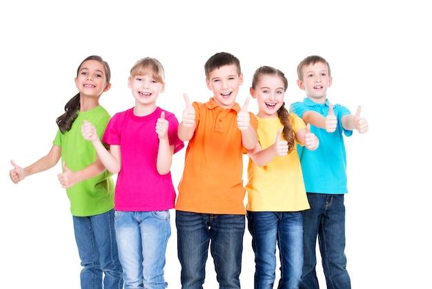 Grupo de niños felices con el pulgar hacia arriba firmar en coloridas camisetas de pie juntos, aislados en blanco.
