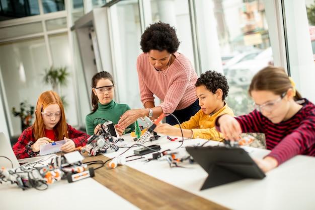 Grupo de niños felices con su profesora de ciencias afroamericana con programación de portátiles juguetes eléctricos y robots en el aula de robótica