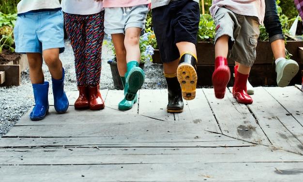 Grupo de niños de jardín de infantes aprendiendo jardinería al aire libre