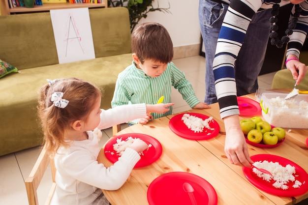 Un grupo de niños en el jardín de infantes sentados en una mesa de madera y comiendo arroz