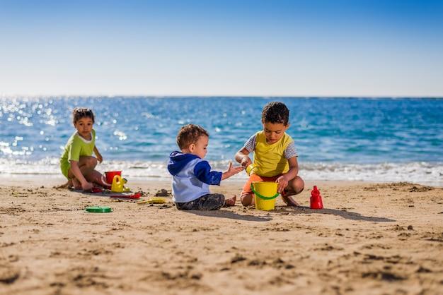 Grupo de niños jugando con juguetes de playa bajo la luz del sol