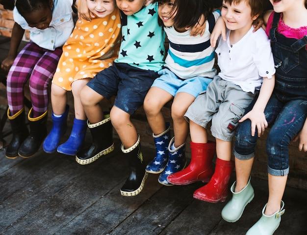 Grupo de niños de kindergarten amigos brazo alrededor sentado y sonriendo divertido