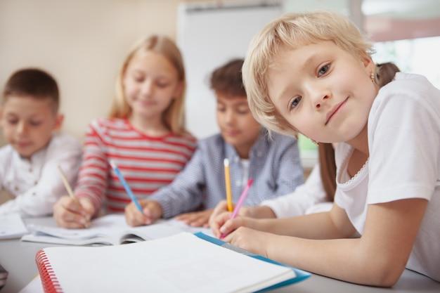 Grupo de niños lindos dibujando juntos en clase de arte