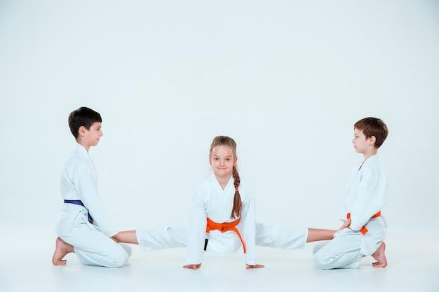 Grupo de niños y niñas en el entrenamiento de aikido en la escuela de artes marciales. estilo de vida saludable y concepto deportivo