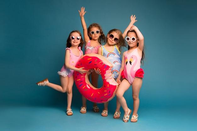 Grupo de niños niñas en trajes de baño y gafas de sol.