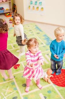 Grupo de niños pequeños bailando y aplaudiendo en las manos