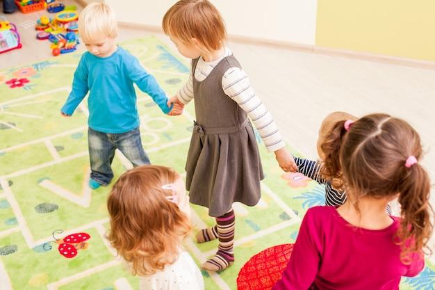Grupo de niños pequeños bailando tomados de la mano y mirando con entusiasmo al niño, que se ríe de alegría.