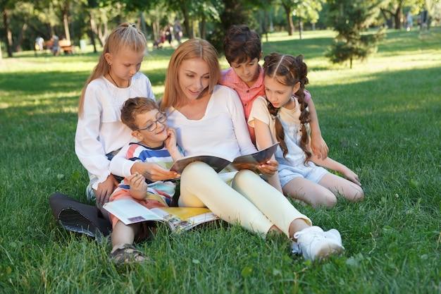 Grupo de niños pequeños disfrutando de su lección al aire libre en el parque con su maestro favorito