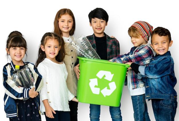 Un grupo de niños pequeños reciclando.