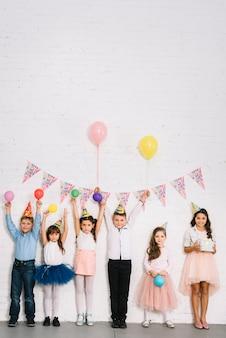 Grupo de niños de pie contra la pared disfrutando de la fiesta de cumpleaños.