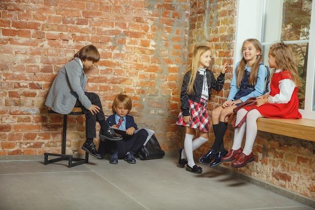 Grupo de niños que pasan tiempo juntos después de la escuela. amigos guapos descansando después de clases antes de comenzar a hacer los deberes