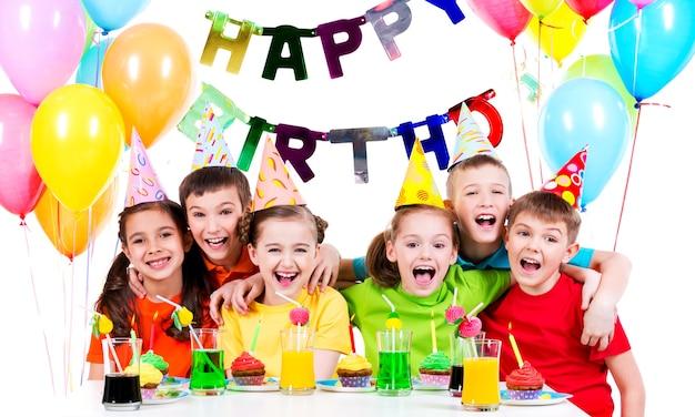 Grupo de niños riendo divirtiéndose en la fiesta de cumpleaños - aislado en un blanco.