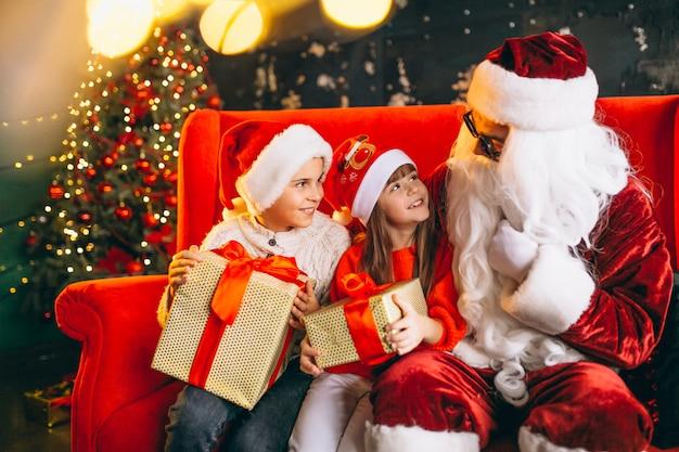 Grupo de niños sentados con santa y regalos en la víspera de navidad