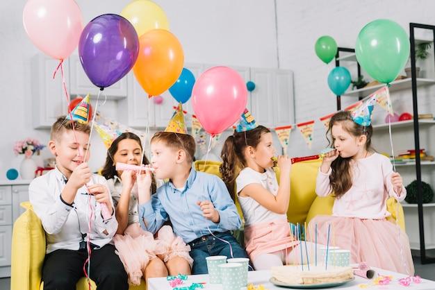 Grupo de niños sentados en un sofá sosteniendo globos de colores y soplando una bocina de fiesta