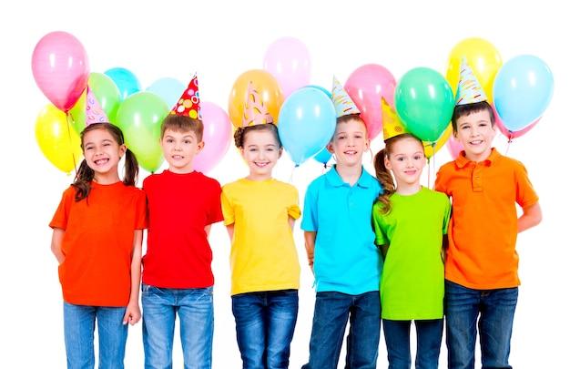 Grupo de niños sonrientes en camisetas de colores y gorros de fiesta con globos en una pared blanca.