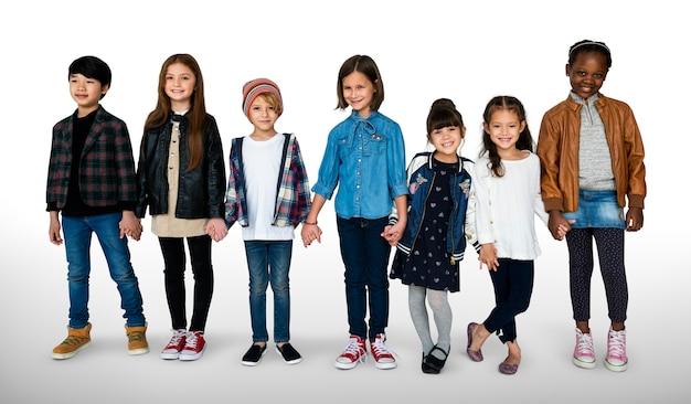 Grupo de niños tomados de la mano expresión cara felicidad sonriendo en blackground blanco