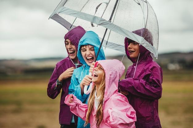 Grupo de niños vestidos con impermeables se ríen y sonríen felices al aire libre con un paraguas en un día lluvioso en su paseo de aventura de campo