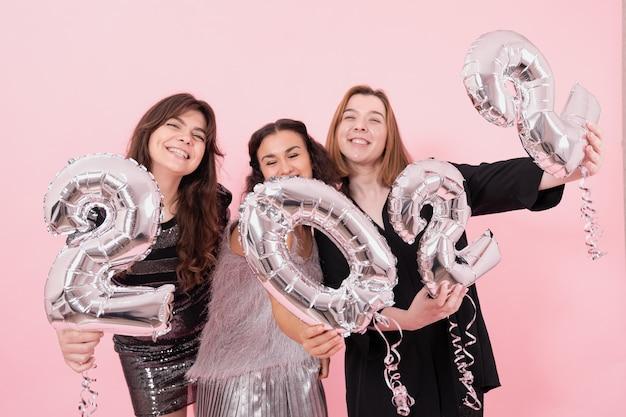 Un grupo de novias con globos plateados en forma de números.