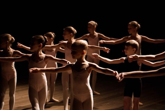 Un grupo numeroso de niños ensayando y bailando ballet.