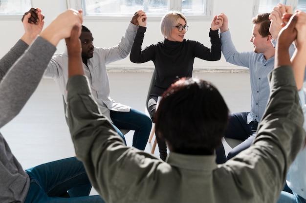 Grupo de pacientes levantando manos