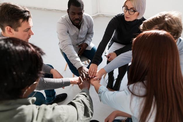 Grupo de pacientes de rehabilitación juntando sus manos