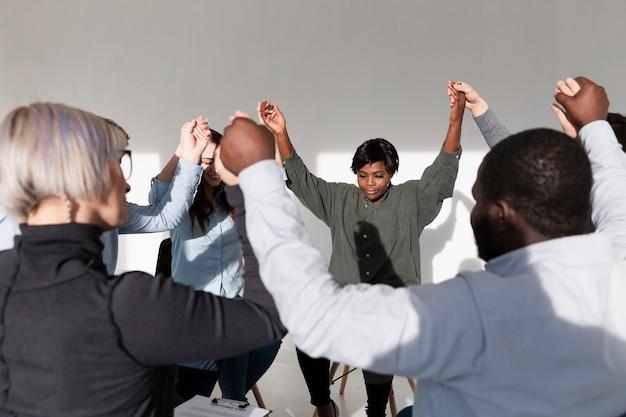 Grupo de pacientes de rehabilitación levantando la mano