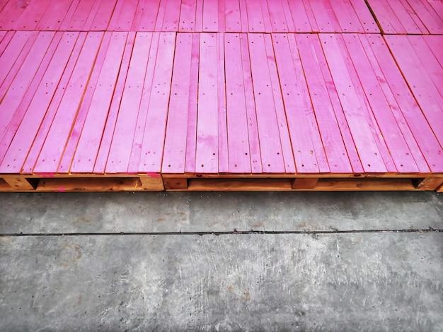Grupo de paletas de madera rosa como pequeño escenario en la calle