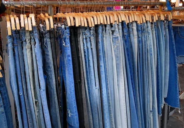 Grupo de pantalones de mezclilla azul colgando de un estante