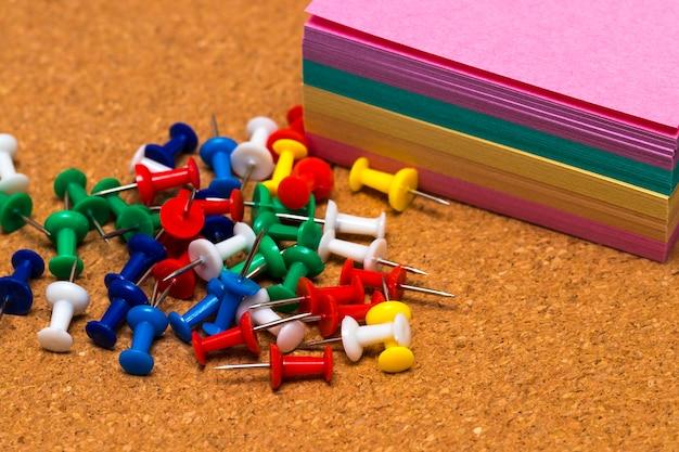 Grupo de pasadores de colores en tablero de corcho