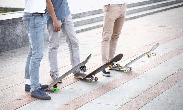 Grupo de patinadores están de pie cerca de sus tablas.